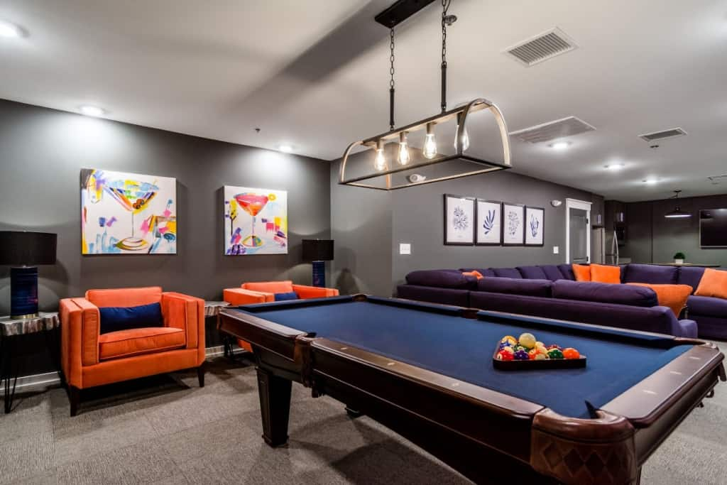 Community amenities like billiards, swimming pool and fitness room at Run Hill Luxury Apartment rentals now leasing in Kill Devil Hills