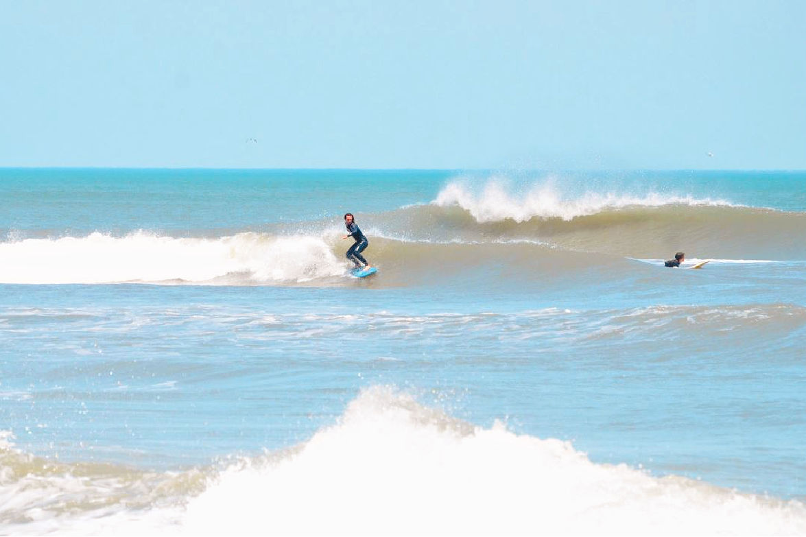 Surfing outer banks beach SAGA Realty and Construction